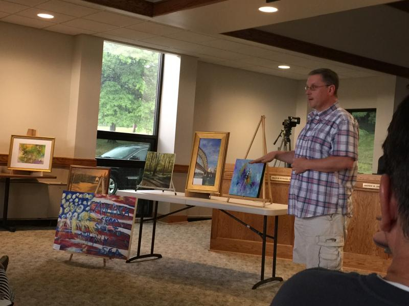 Lance explaining why he chose the background for his Meek cabin painting.